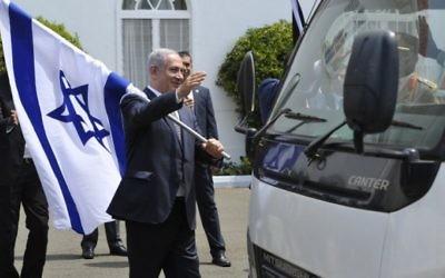 Le Premier ministre Benjamin Netanyahu avec un drapeau israélien après une conférence de presse commune avec le président du Kenya, à Nairobi, le 5 juillet 2016. (Crédit : AFP/Simon Maina)