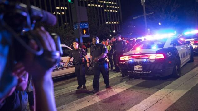 Des passants près des barricades de  la police après des coups de feu à Dallas, Texas, le 7 juillet 2016, qui ont tué cinq policiers pendant une manifestation pacifique jeudi soir contre la violence policière. (Crédit : AFP/Laura Buckman)