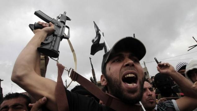Des musulmans sunnites brandissent leurs armes pendant les funérailles de Sheikh Ahmad Abdel Wahed et de ses compagnons religieux à al-Bireh, sa ville natale du nord de Beyrouth, le 21 mai 2012. (Crédit : AFP/Joseph Eid)