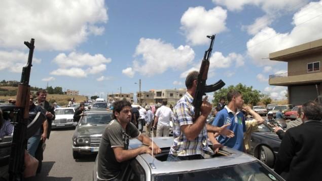 Des musulmans sunnites brandissent leurs armes pendant qu'ils escortent pour ses funérailles l'ambulance transportant le corps de Sheikh Ahmad Abdel Wahed, qui a été tué par des militaires quand son convoi ne s'est pas arrêté à un checkpoint à l'entrée d'al-Bireh, sa ville natale du nord de Beyrouth, le 21 mai 2012. (Crédit : AFP/Joseph Eid)