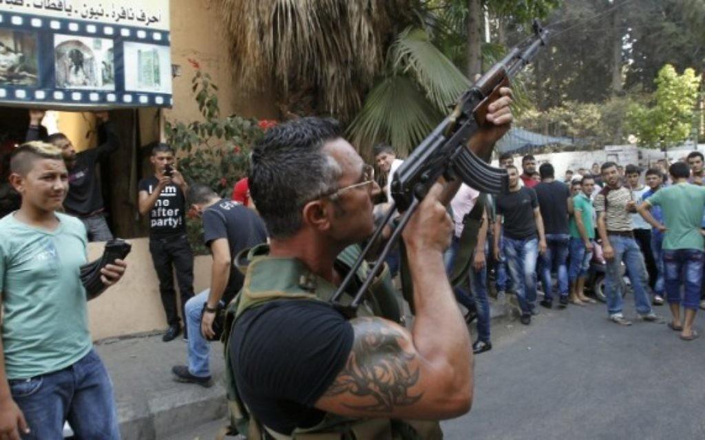 Un Libanais armé pendant la procession funéraire de Hamad al-Moqdad, une des victimes libanaises d'un attentat à la voiture piégée qui a tué des dizaines de personnes dans un bastion du Hezbollah à Beyrouth, le 16 août 2013. (Crédit : AFP/Anwar Amro)