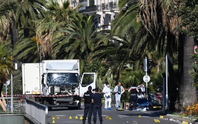 Des officiers et des policiers cherchent des preuves à proximité du camion utilisé sur la promenade des Anglais dans la ville Côte d'Azur de Nice le 15 juillet 2016, pour tuer une foule d'individus venue admirer le feu d'artifices  (Crédit : AFP/ANNE-CHRISTINE POUJOULAT)
