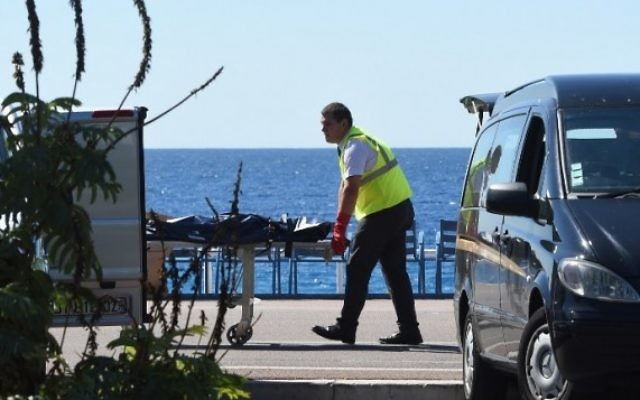 Un médecin légiste évacue un corps, sur la Promenade des Anglais, sur la Côte d'Azur, dans la ville de Nice, le 15 juillet 2016, après qu'un homme armé ait précipité un camion dans la foule venue célébrer la fête nationale, tuant au moins 84 personnes (Crédit : AFP Photo/Boris Horvat)