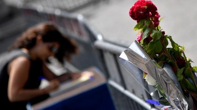 Une femme signe un livre de condoléances devant l'ambassade de France à Rome, le 15 juillet 2016, après l'attaque terroriste mortelle de Nice (Crédit : AFP Photo/Tiziana Fabi)