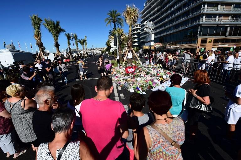 Les gens déposent des fleurs, des bougies et des messages à un mémorial improvisé à Nice le 16 juillet 2016, en hommage aux victimes de l'attaque du 14 juillet sur la promenade des Anglais, qui a tué au moins 84 personnes et fait des centaines de blessés. (Crédit : Giuseppe Cacace/AFP)