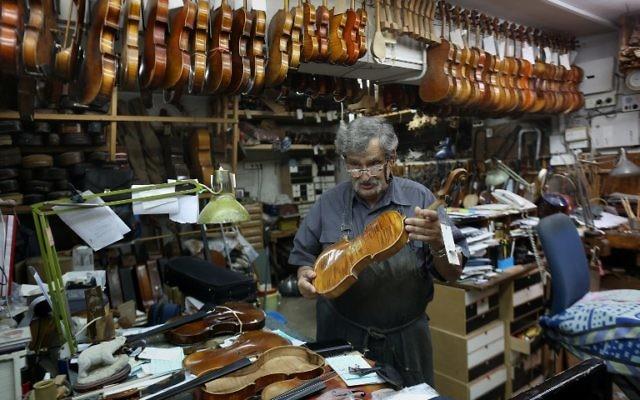 Le luthier israélien Amnon Weinstein montre un violon de sa collection de violons restaurés qui étaient auparavant la propriété de Juifs européens pendant l'Holocauste dans son atelier à Tel Aviv le 15 juillet 2016. (Crédit : AFP / MENAHEM KAHANA)