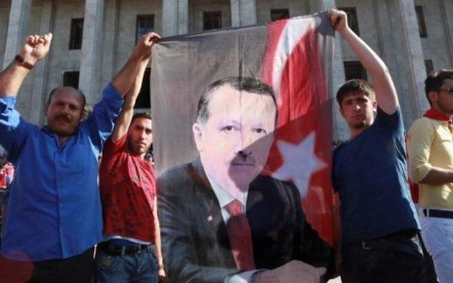 Des partisans du président turc Recep Tayyip Erdogan tiennent une bannière avec son portrait pendant un rassemblement devant le parlement turc, réuni en session extraordinaire à la suite d'une tentative de coup d'Etat, à Ankara, le 16 juillet 2016. (Crédit : AFP/Adem Altan)