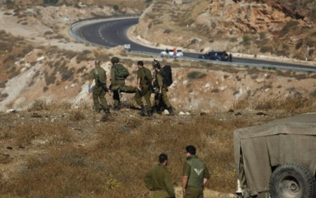 Des soldats israéliens évacuent un soldat blessé après l'explosion d'une grenade près du village de Majdal Shams, sur le plateau du Golan, le 17 juillet 2016. (Crédit : AFP/Jalaa Marey)