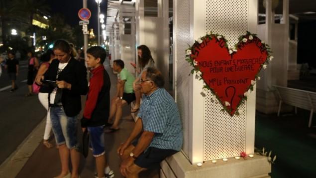 """Un homme près d'un panneau en forme de cœur sur lequel il est inscrit : """"Stop au massacre... Nos enfants massacrés pour une guerre... M. le Président ?"""" sur la Promenade des Anglais, à Nice, le 17 juillet 2016. (Crédit : AFP/Valéry Hache)"""