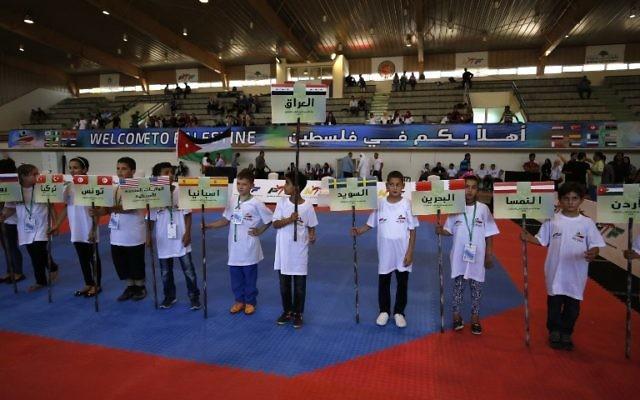 Des enfants portent des bannières portant les noms et les drapeaux des pays participant au championnat international de taekwondo à Birzeit, à Ramallah, en Cisjordanie, le 18 juillet 2016. (Crédit : AFP/Abbas Momani)