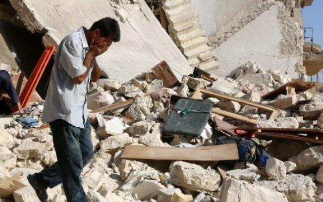 Un Syrien réagit alors que les secouristes recherchent des victimes sous les décombres d'un bâtiment effondré suite à une frappe aérienne sur le quartier rebelle de Sakhur dans la ville du nord, Alep, le 19 juillet, 2016 (Crédit : AFP / Thaer Mohammed)