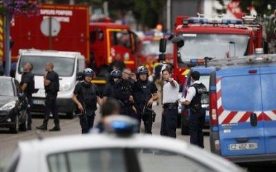 Des policiers et des pompiers français sur les lieux d'une prise d'otages dans une église de Saint-Etienne-du-Rouvray, dans le nord ouest de la France, le 26 juillet 2016. (Crédit : Charly Triballeau/AFP)