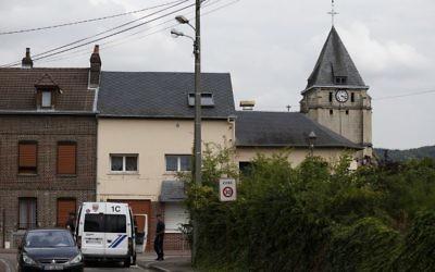 Les policiers montent la garde derrière l'église Saint-Etienne de Saint-Etienne-du-Rouvray le 26 Juillet 2016, suite à une attaque par deux hommes armés de couteaux. (Crédit : CHARLY TRIBALLEAU/AFP)