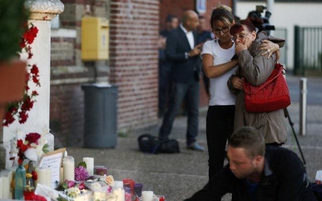 Deux femmes près des fleurs et des messages affichés en face de la mairie de la ville normande de Saint-Etienne du Rouvray, en hommage au prêtre tué dans l'église de la ville, une attaque revendiquée par le groupe djihadiste de l'Etat islamique, le 26 juillet 2016. (Crédit : AFP/ CHARLY TRIBALLEAU)