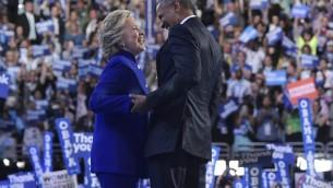Le président américain Barack Obama rejoint la candidate démocrate à la présidentielle Hillary Clinton après son discours à la Convention nationale démocratique au Wells Fargo Center à Philadelphie, en Pennsylvanie, le 27 juillet 2016. (Crédit : AFP / MANDEL NGAN)