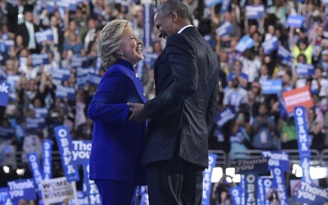 Le président américain Barack Obama rejoint la candidate démocrate à la présidentielle Hillary Clinton après son discours à la Convention nationale démocratique au Wells Fargo Center à Philadelphie, en Pennsylvanie, le 27 juillet 2016. (Crédit : Mandel Ngan/AFP)