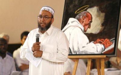 L'imam d'Oissel Abdellatif Hmito prononce un discours près d'un portrait du père Jacques Hamel, assassiné pendant une attaque terroriste, pendant une veillée en l'église Sainte-Thérèse de Saint-Etienne du Rouvray, le 30 juillet 2016. (Crédit : AFP/Charly Triballeau)