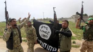 Des membres de l'unité paramilitaire irakienne Mobilisation Populaire célèbrent la reprise du village d'Albu Ajil, près de la ville de Tikrit, qui était détenu par l'Etat islamique, en agitant un drapeau du groupe terroriste, le 9 mars 2015 (Crédit : AFP/Ahmad al-Rubaye)