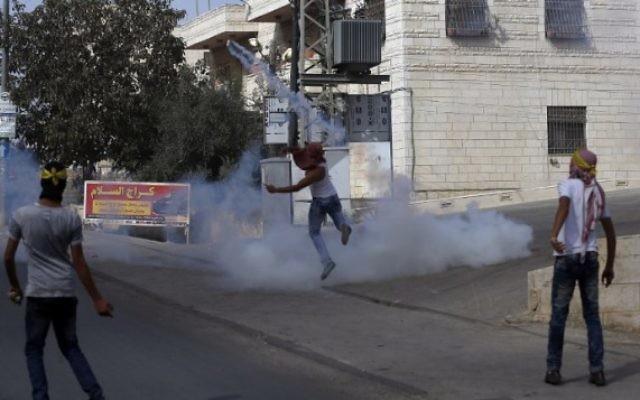 Un jeune Palestinien masqué renvoie des gaz lacrymogènes sur les garde-frontières israéliens pendant des affrontements dans le village palestinien d'al-Ram, entre Jérusalem et Ramallah, en Cisjordanie, le 22 octobre 2015. (Crédit : AFP/Abbas Momani)