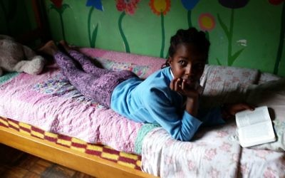 Une fille lit la Bible dans son lit au Centre d'Addis-Abeba AHOPE pour les orphelins séropositifs, le 7 juillet 2016 (Crédit : Raphael Ahren / Times of Israel)