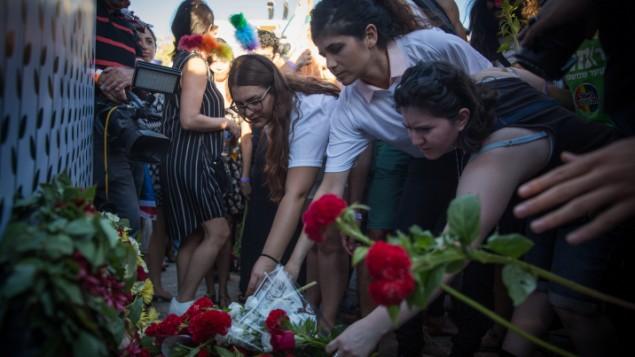 Les participants déposent des fleurs à l'endroit où Shira Banki, 16 ans, a été poignardée à mort lors de la Gay Pride de l'année dernière, pendant la Gay Pride annuelle à Jérusalem, qui a compté plus de 25 000 participants, le 21 juillet 2016. (Crédit : Hadas Parush/Flash90)