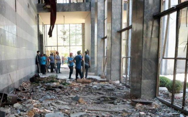 Des ouvriers inspectent et nettoient les débris après les bombardements de la Grande Assemblée nationale de Turquie par des avions participant à la tentative de coup d'Etat militaire, à Ankara, le 16 juillet 2016. (Crédit : AFP/Adem Altan)