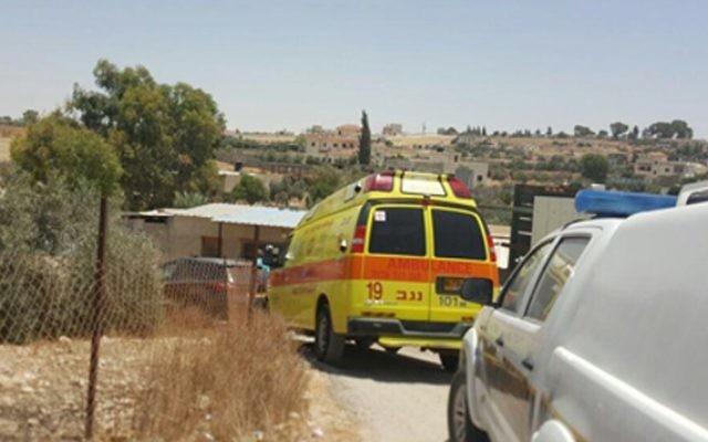 Une ambulance de Magen David Adom à l'endroit où deux enfants sont morts après avoir été oubliés dans une voiture, dans le Conseil régional de Al Kaum dans le Néguev, le 22 juin 2016 (Crédit : Magen David Adom)