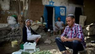 Atenkut Setataw (à dr.), avec sa femme Alesa Netere (à g.) et un voisin, lors d'une cérémonie du café pour les visiteurs devant leur maison de Gondar (Crédits : Miriam Alster / Flash 90)