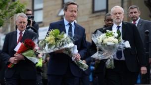 Le Premier ministre britannique David Cameron (centre), la députée travailliste Hilary Benn (à g.) et le chef du Parti travailliste Jeremy Corbyn (à dr.), s'apprêtent à déposer des fleurs en mémoire de la députée travailliste Jo Cox, tuée lors d'un meeting, à Bristall, nord de l'Angleterre, le 17 juin 2016. (Crédits : AFP / Oli Scarff)