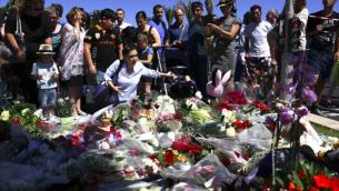 Les gens déposent des fleurs dans les rues de Nice pour rendre hommage aux victimes le lendemain de l'attaque, le 15 juillet 2016. (Crédit : AFP/Anne-Christine Poujoulat)