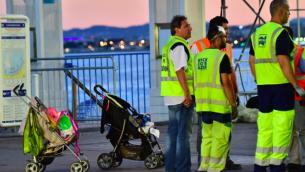 Les éboueurs se rassemblent près des poussettes abandonnées, alors qu'ils se préparent à nettoyer la Promenade des Anglais, le 15 juillet 2016 à Nice, le jour suivant la mortelle attaque. (Crédit : AFP / GIUSEPPE CACACE)
