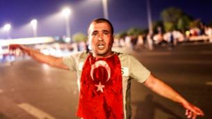 Un homme couvert de sang se trouve près du pont du Bosphore au milieu d'affrontements militaires turcs avec des personnes à l'entrée du pont à Istanbul le 16 juillet 2016. (Crédit : AFP / Bulent KILIC)