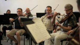 """L'Israël Camerata Jerusalem Orchestra jouent avec des """"Violins de l'espoir"""",le 13 juillet 2016. (Crédit : AFP / MENAHEM KAHANA)"""