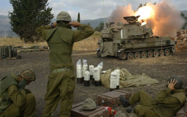 Les soldats israéliens couvrent leurs oreilles alors qu'ils tirent des obus d'artillerie dans le sud du Liban depuis l'extérieur de Kiryat Shmona, dans le nord d'Israël au cours de la seconde guerre du Liban, le 22 juillet, 2006. (Crédit : Pierre Terdjman / Flash90)