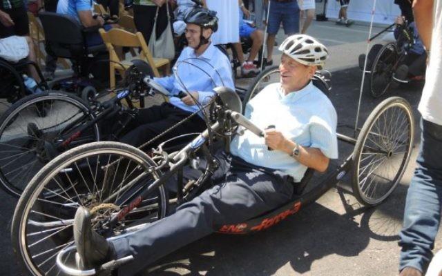 Le ministre du Tourisme Yariv Levin (à gauche) et le maire de Tel Aviv Ron Huldai essaient des handbikes sur la piste cyclable nouvellement adaptée, le 28 juillet 2016 (Crédit : Melanie Lidman/Times of Israel)