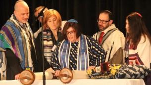 La rabbin Denise Eger, au centre, lit la Torah pendant son intronisation comme présidente de la Conférence centrale des rabbins américains, le 16 mars 2015. (Crédits : David A.M. Wilensky)