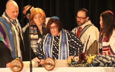 La rabbin Denise Eger, au centre, lit la Torah pendant son intronisation comme présidente de la Conférence centrale des rabbins américains, le 16 mars 2015. Illustration. (Crédit : David A.M. Wilensky)