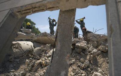 Des soldats des unités de recherche et sauvetage du Commandement de la Défense passive de l'armée israélienne nettoient des débris d'une fausse frappe de roquette pendant un exercice à grande échelle, à Zikim, près de la frontière de la bande de Gaza, le 3 juillet 2016. (Crédit : unité des porte-paroles de l'armée israélienne)
