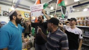 """Des manifestants palestiniens avec des drapeaux et une pancarte """"Boycott de l'occupation et de ses produits"""" pendant une manifestation dans un supermarché Rami Levy de l'implantation juive de Cisjordanie Moddin Illit, le 24 octobre 2012. (Crédit : Issam Rimawi/Flash90)"""