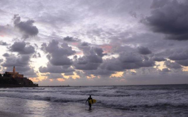 Un surfeur solitaire le long de la côte de Tel Aviv. (Crédit : Tomer Neuberg/Flash90)