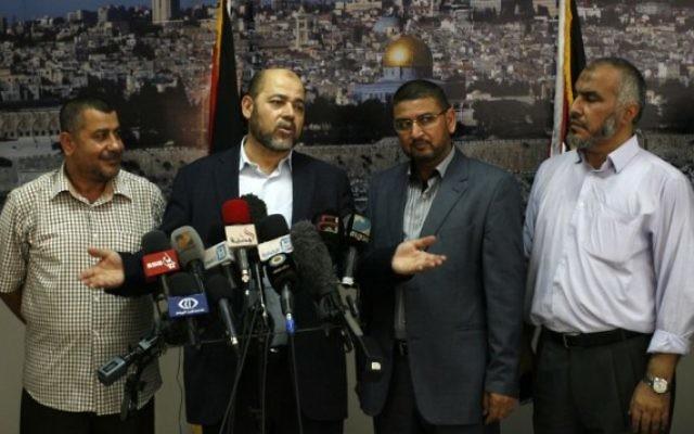 Moussa Abu Marzouk (deuxième à gauche), responsable du Hamas, s'adresse aux médias depuis le poste-frontière de Rafah, dans le sud de la bande de Gaza, après des négociations avec Le Caire, le 28 août 2014. (Crédit : Abed Rahim Khatib/Flash90)