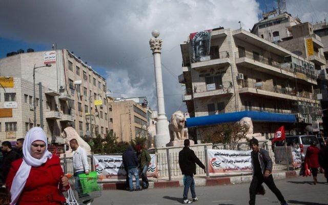 Des Palestiniens vus sur la place Manara au centre de Ramallah, siège de l'Autorité palestinienne, le 14 février 2015. (Crédit : Miriam Alster / FLASH90)