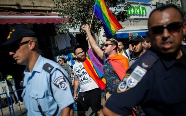Des membres de la communauté LGBT entourés de centaines de policiers israéliens manifestent tourte de Jaffa, à Jérusalem, le 14 août 2015, après l'attaque au couteau mortelle pendant la Gay Pride annuelle de la ville le 30 juillet 2015. (Crédit : Yonatan Sindel/Flash90).