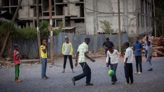 Des membres de la communauté juive éthiopienne Falash Mura jouent au foot dans la rue, après avoir pris part à la prière à la synagogue à Gondar, Ethiopie, pendant Pessah, le 26 avril 2016 (Crédit : Miriam Alster/FLASH90)