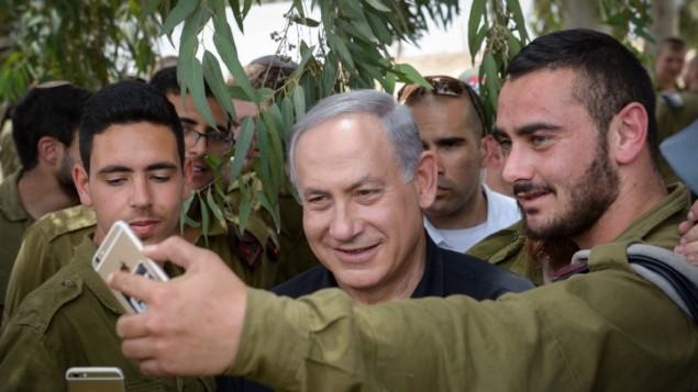 Le Premier ministre Benjamin Netanyahu avec des soldats israéliens pendant une visite sur la frontière sud d'Israël avec la bande de Gaza, le 3 mai 2016. (Crédit : GPO/Amos Ben Gershom)