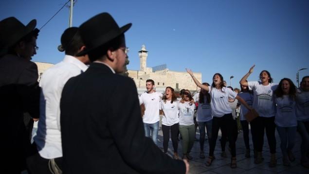 Des hommes juifs ultra-orthodoxes s'en prennent à des hommes et femmes juifs des mouvements conservateur et réformé alors qu'ils participaient à un service de prière devant le mur Occidental, dans la vieille ville de Jérusalem, le 16 juin 2016 (Hadas Parush/Flash90)