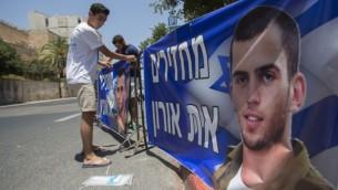 """Le frère du soldat israélien décédé Oron Shaul organise une manifestation devant la résidence du premier ministre Benjamin Netanyahu à Jérusalem, le 30 juin 2016. Les panneaux disent """"Rendez Oron"""". (Crédit : Yonatan Sindel/Flash90)"""