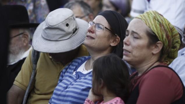 La famille de Hallel Yaffa Ariel pleure lors de l'enterrement dans l'implantation juive de Kiryat Arba, en Cisjordanie, le 30 juin 2016. Plus tôt ce jour là, un Palestinien âgé de 17 ans s'était introduit dans leur maison et avait poignardé à mort Hallel, 13 ans, alors qu'elle dormait dans sa chambre (Crédit : Yonatan Sindel/Flash90)