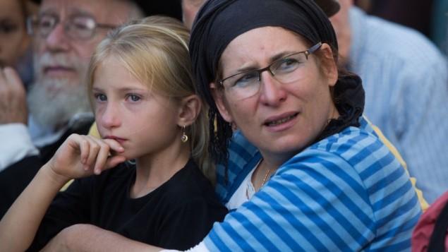 La mère et l'une des petites sœurs de Hallel Yaffa Ariel lors de ses funérailles, dans l'implantation juive de Kiryat Arba, en Cisjordanie, le 30 juin 2016. (Crédit : Yonatan Sindel/Flash90)