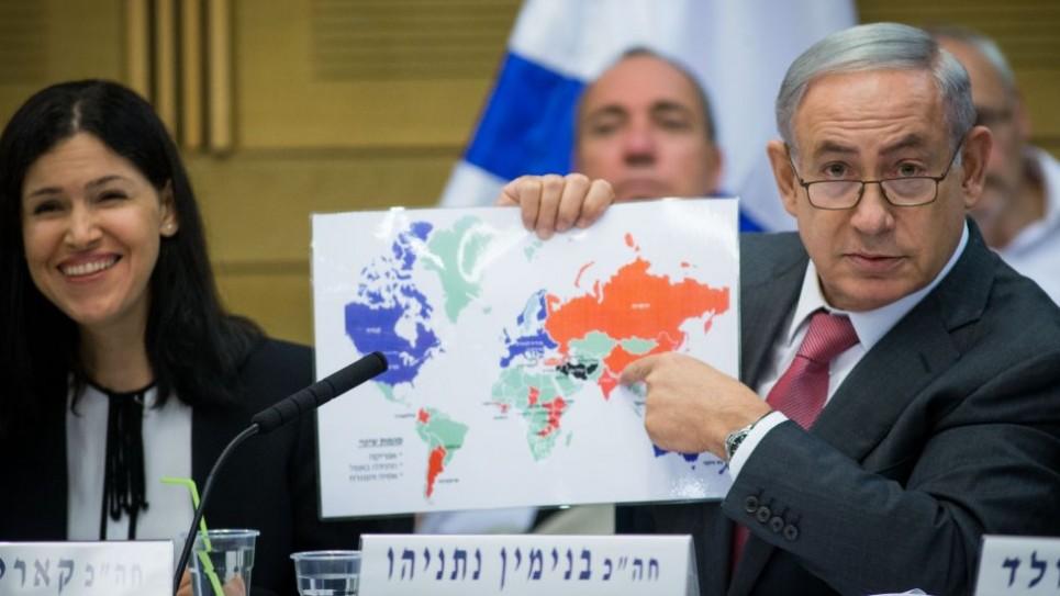 Le Premier ministre Benjamin Netanyahu montre sa carte des relations d'Israël avec le monde, lors d'une session avec la Commission de contrôle d'Etat de la Knesset, le 25 juillet 2016. A son côté, la présidente de la commission Karin Elharar de Yesh Atid (Crédit : Yonatan Sindel/Flash90)